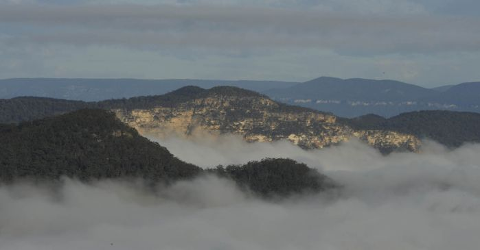 Mist sitting over rocky cliffs