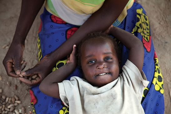 Child laying in mother's lap in zambia