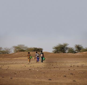 Women walking across desert to collect water with buckets