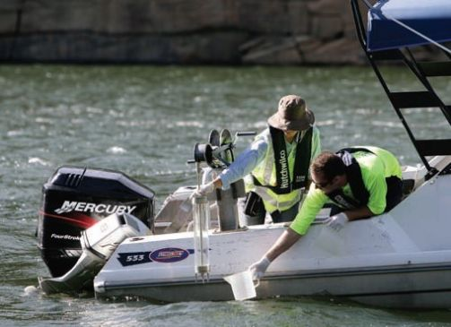 two staff testing water using a boat