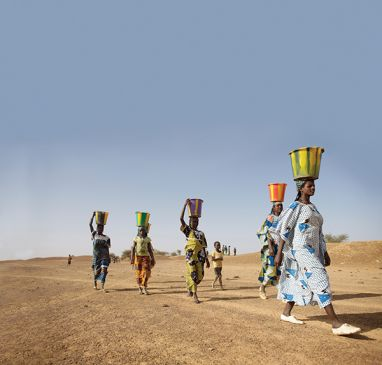 Women walking walking with water buckets on heads