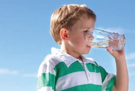a boy drinks from a glass