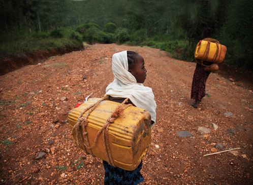 Child carrying water box in ethiopia