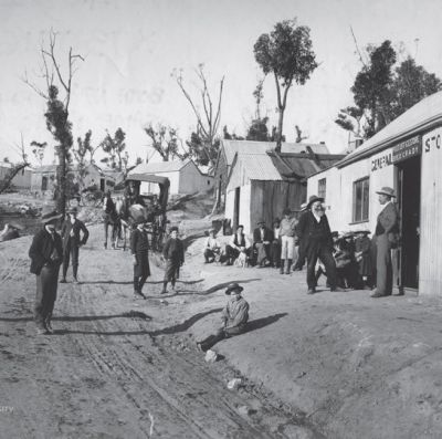 turn of the century photograph showing huts and a dirt road with people standing around