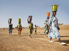 Women walking in desert with buckets on head