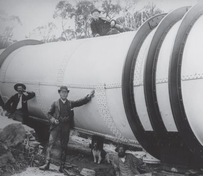 an old photograph of workers on the Upper Nepean Scheme, standing near a big pipeline