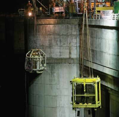a crane lifts a concrete block from the water