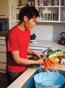 Man washing vegies in a bucket