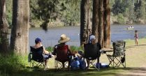 People relaxing on chairs by riverbank