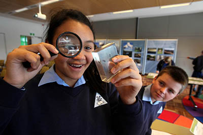 Student looking through magnifying glass