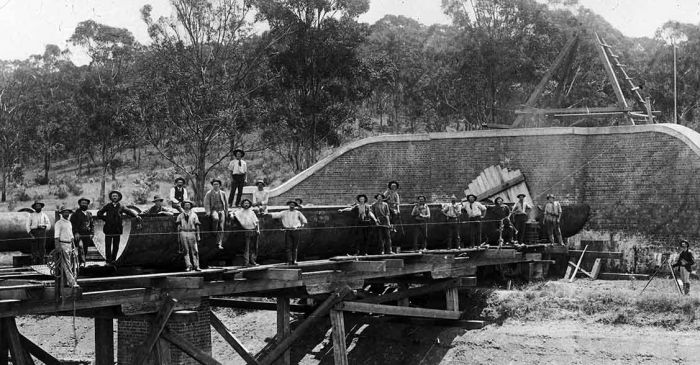 Workers standing on railway aqueduct