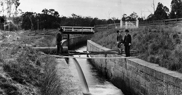 three men standing next to Upper Canal pipe