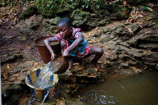 Child gathering water in Sierra Leone
